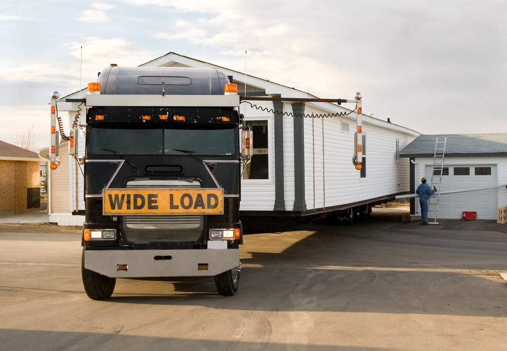 semi-truck backing in a mobile home with wide load sign