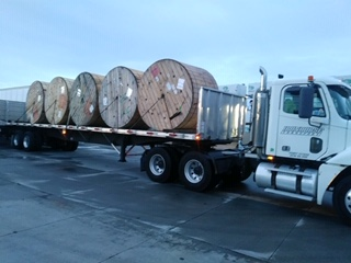 flatbed truck hauling large spools of cable to a NYC job site by Iron Horse Transport